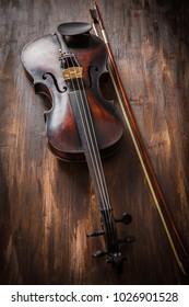 Old violin in vintage style on wood background