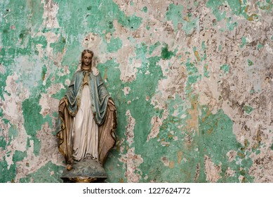 Old Virgin Mary statue, peeling paint grunge wall background of an abandoned building