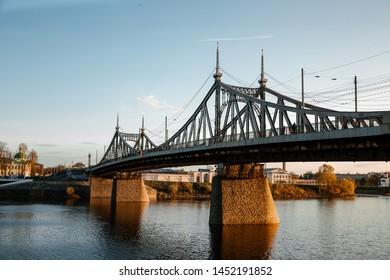 The old Volga bridge in Tver over the Volga river at sunset