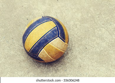 old volleyball rolling on the concrete floor in soft focus ,vintage tone