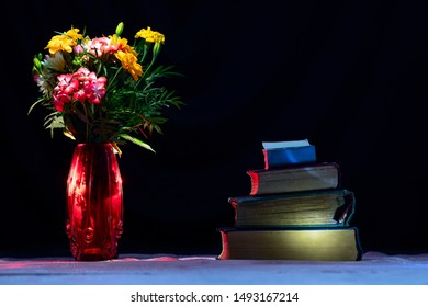 Old voluminous tomes written in ancient times stacked on the reading table of dark calm night. A bouquet of fresh wildflowers in a red vase adorns the table.