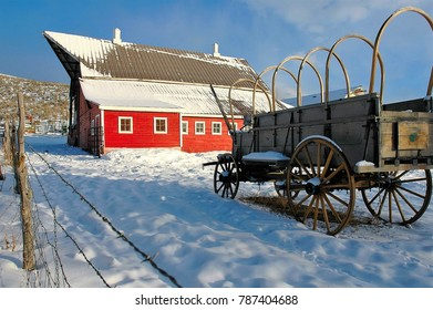 Old wagon and red barn seem juxtaposed with each other.  Each one  symbolizing a different era.