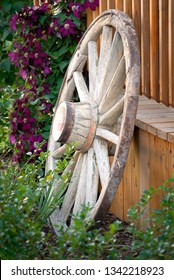 Old wagon wheel against fence in flower garden for decoration landscaping