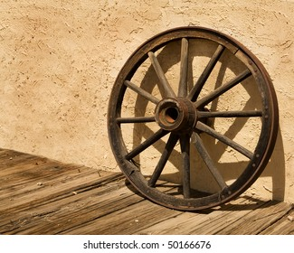 An old wagon wheel, an iconic symbol of the American West, sits on a wooden sidewalk and leans against a stucco wall.  It's a sunny day and the wheel casts an interesting shadow on the wall.