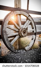 Old wagon wheel leaning against a fence at sunset.