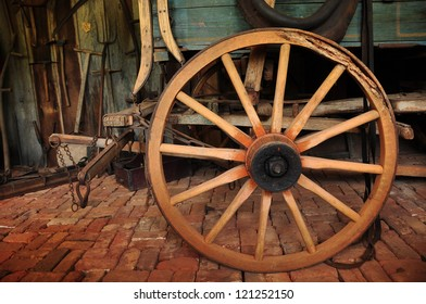 Old Wagon Wheel on Wagon on Brick Floor surrounded by old tools