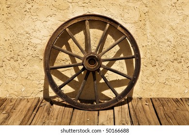An old wagon wheel sits on a wooden sidewalk and leans against a stucco wall, in a scene from the American West.  The wheel casts interesting shadows against the wall.