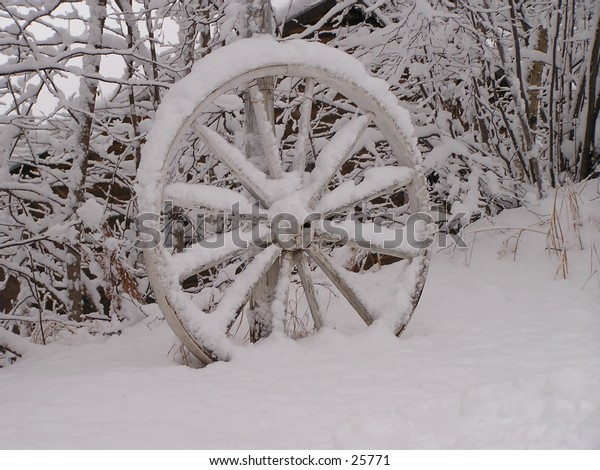 old wagon wheel under snow - first november snow 2004 in North Laurentian, Quebec