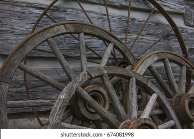 Old wagon wheels leaning against a log home.