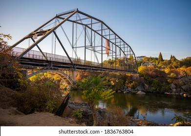 Old Walking bridge in Folsom CA with fall colors and trees over the American river