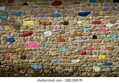Old wall background. Irregular pattern with mixed natural and painted stones.