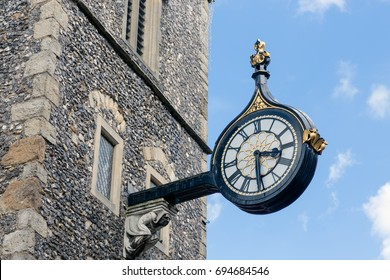 Old wall clock on side ancient tower downtown in Canterbury city, England