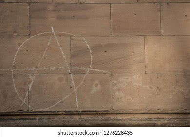 Old wall of a historical building with written anarchy sign