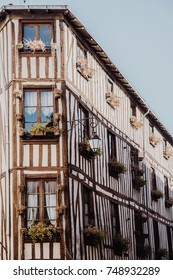 The old wall of the medieval french building with the windows decorated with flowers