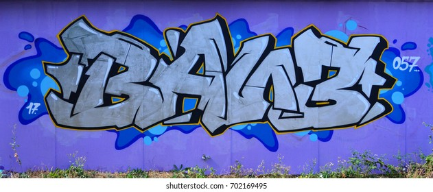 The old wall, painted in color graffiti drawing silver chrome aerosol paints. Background image on the theme of drawing graffiti and street art