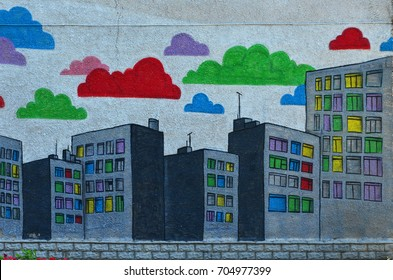 The old wall, painted in color graffiti drawing with aerosol paints. An image of a multitude of skyscrapers with multi-colored windows
