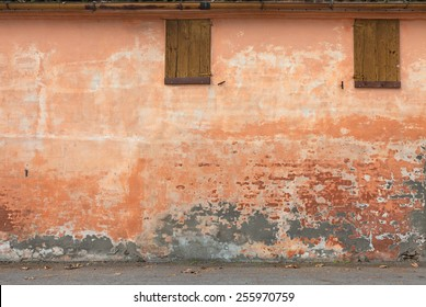 old wall with peeling paint, scratched stained plaster and closed windows - grunge background of urban decay