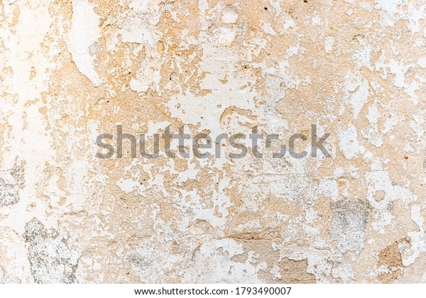 Old wall with peeling paint white. Old textured concrete wall painted white color.