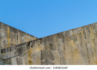 Old wall as a triangle formation. Two stone walls in a row. Triangular structure. Stone masonry intersect optically in perspective. Abstract background. stone wall.
