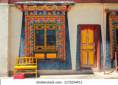 Old wall with window painted colorful in Tibetan style. Songzanlin Temple also known as the Ganden Sumtseling Monastery, is a Tibetan Buddhist monastery in Zhongdian city( Shangri-La), Yunnan China.
