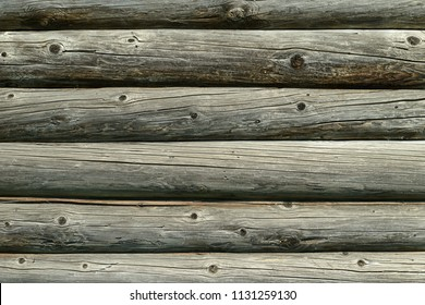 old wall of wooden round logs of gray color