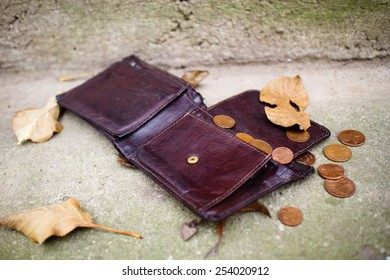 Old wallet with euro coins on concrete floor.