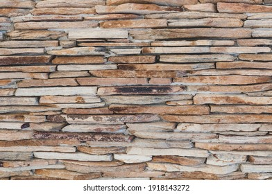 Old walls thin sandstone slabs, masonry layered, vintage stone wall background. Grungy texture for 3d design. Close-up horizontal photography.