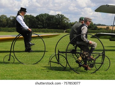 Old Warden airfield, Bedfordshire, UK - 08/06/17: Cyclists riding 1878 Starley quadricycle (r) and 1885 Dan Albone high wheeler 'penny farthing' (l) at Shuttleworth Collection's 2017 Edwardian Pagent.