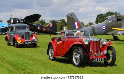 Old Warden, Bedfordshire, UK - 08/06/17: 1946 MG Midget TC (r) 1938 Hillman Minx (l), passing 1938 Westland Lysander (161 special duties Sqn) at Shuttleworth Collection's 2017 Edwardian Pagent.