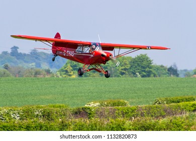 OLD WARDEN, BEDFORDSHIRE, UK – MAY 6, 2018: Having opened the Season Premiere and 100 Years of the RAF airshow with a banner tow, 1961 Piper PA-18-150 Super Cub G-SVAS comes in to land at Old Warden.