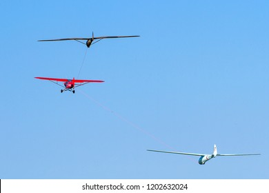 OLD WARDEN, BEDFORDSHIRE, UK – MAY 6, 2018: Piper PA-18-150 Super Cub carries out a twin tow of Eon Olympia VV400 & Kirby Radar Kite gliders at Old Warden during the Premier &100 Years of RAF airshow.