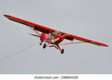 OLD WARDEN, BEDFORDSHIRE, UK – OCTOBER 5, 2014: 1961 Piper PA-18-150 Super Cub C/N 18-7605 (G-SVAS) approaches to land at Old Warden after launching the EoN Type 7 S.G.38 Primary glider at Old Warden.