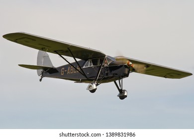OLD WARDEN, BEDFORDSHIRE, UK – OCTOBER 5, 2014: De Havilland DH.80A Puss Moth G-ABLS carries out a display at Old Warden airfield during the Shuttleworth Airshow.