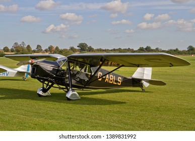 OLD WARDEN, BEDFORDSHIRE, UK – OCTOBER 5, 2014: De Havilland DH.80A Puss Moth G-ABLS stands on the flight line at Old Warden airfield prior to the Shuttleworth Airshow.