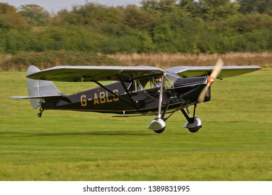 OLD WARDEN, BEDFORDSHIRE, UK – OCTOBER 5, 2014: De Havilland DH.80A Puss Moth G-ABLS lands at Old Warden airfield during the Shuttleworth Airshow.