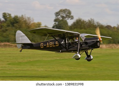 OLD WARDEN, BEDFORDSHIRE, UK – OCTOBER 5, 2014: De Havilland DH.80A Puss Moth G-ABLS approaches to land at Old Warden airfield prior to the Shuttleworth Airshow.