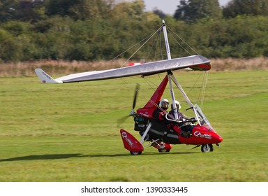 OLD WARDEN, BEDFORDSHIRE, UK – OCTOBER 5, 2014: A red coloured P&M Aviation Quik 912S GT-450 Microlight lands at Old Warden airfield before the start of the Shuttleworth Airshow.