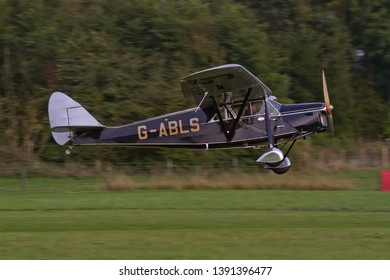 OLD WARDEN, BEDFORDSHIRE, UK – OCTOBER 5, 2014: De Havilland DH.80A Puss Moth G-ABLS, a British three-seater high-wing monoplane aeroplane, takes off from Old Warden during the Shuttleworth Airshow.