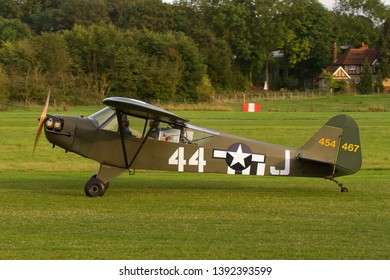 OLD WARDEN, BEDFORDSHIRE, UK – OCTOBER 5, 2014: Piper J3C-65 Cub 454467 G-BILI taxis out to depart from Old Warden airfield at the end of the Shuttleworth Airshow.