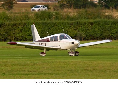 OLD WARDEN, BEDFORDSHIRE, UK – OCTOBER 5, 2014: Piper PA-28-180 Cherokee C G-ATTX takes off from Old Warden airfield at the end of the Shuttleworth Airshow.