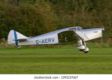 OLD WARDEN, BEDFORDSHIRE, UK – OCTOBER 5, 2014: 1936 Miles M11A Whitney Straight G-AERV takes off from Old Warden airfield during the Shuttleworth Airshow.