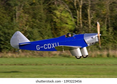 OLD WARDEN, BEDFORDSHIRE, UK – OCTOBER 5, 2014: Chilton DW.1 G-CDXU, a British light sporting monoplane from the 1930s, takes off from Old Warden airfield at the end of the Shuttleworth Airshow.