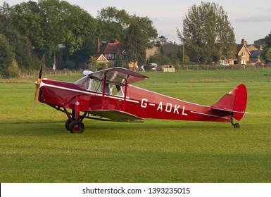 OLD WARDEN, BEDFORDSHIRE, UK – OCTOBER 5, 2014: De Havilland DH-87B Hornet Moth G-ADKL taxis out for departure at Old Warden airfield at the end of the Shuttleworth Airshow.