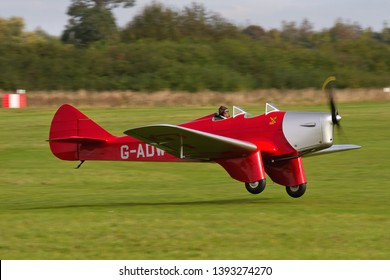 OLD WARDEN, BEDFORDSHIRE, UK – OCTOBER 5, 2014: 1934 Miles M2W Hawk Trainer G-ADWT, a British two-seat training monoplane, takes off from Old Warden during the Shuttleworth Airshow.
