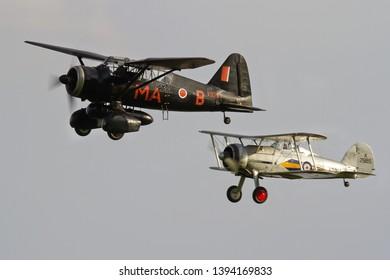 OLD WARDEN, BEDFORDSHIRE, UK – OCTOBER 5, 2014: Westland Lysander IIIA V9367 G-AZWT and Gloster Gladiator L8032 K7985 (G-AMRK) display together at Old Warden during the Shuttleworth Airshow.