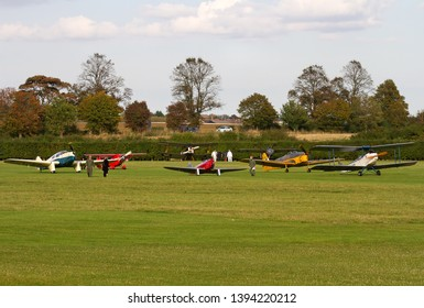 OLD WARDEN, BEDFORDSHIRE, UK – OCTOBER 5, 2014: A varied assortment of aircraft, dating from the early 1900s through to the mid 1900s, are assembled by the threshold of the grass strip at Old Warden.