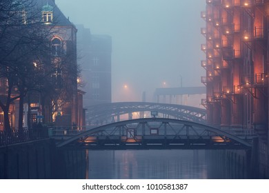 Old warehouse district in mysterious fog. Water canal in Hamburg, Germany.