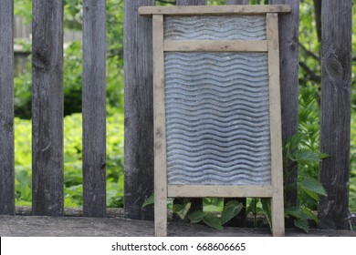 An old washboard stands near a wooden fence in the village. A tool for hand washing used in the last century. Metal washing board.