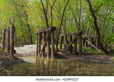 Old washed out wooden bridge in the North Central Illinois woods as the sunlight comes through the trees.