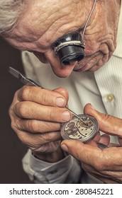 old watchmaker repairing clocks